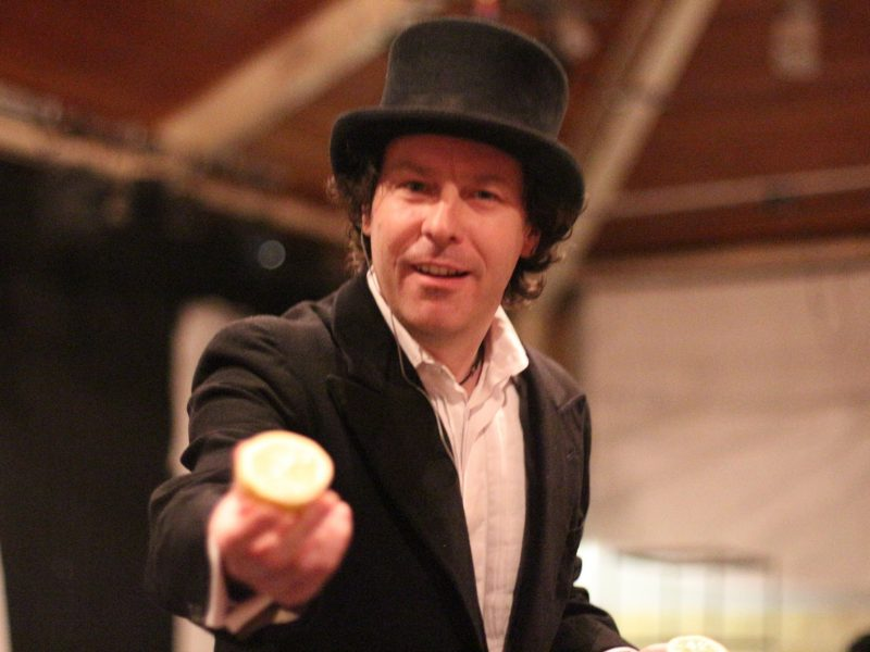 Jon, wearing a top hat and frock coat, offers a lemon for you to smell.