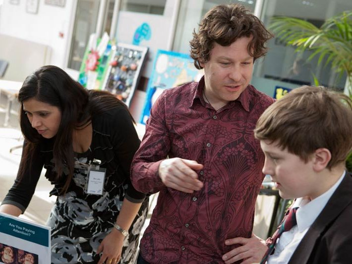 Jon talks to a young delegate at a science fair.