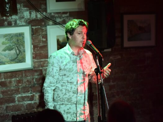 Jon performs stand up comedy in a local venue.