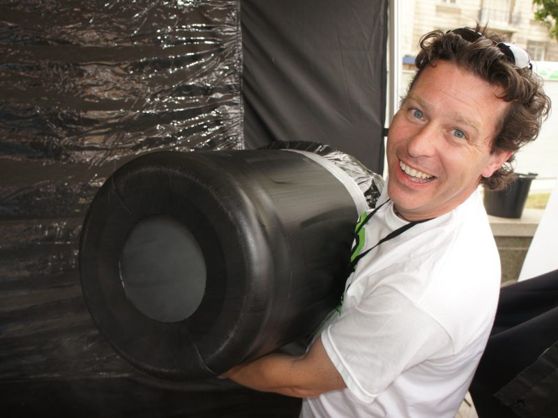 In his hands, Jon holds a large plastic barrel with hole and stage smoke issuing.