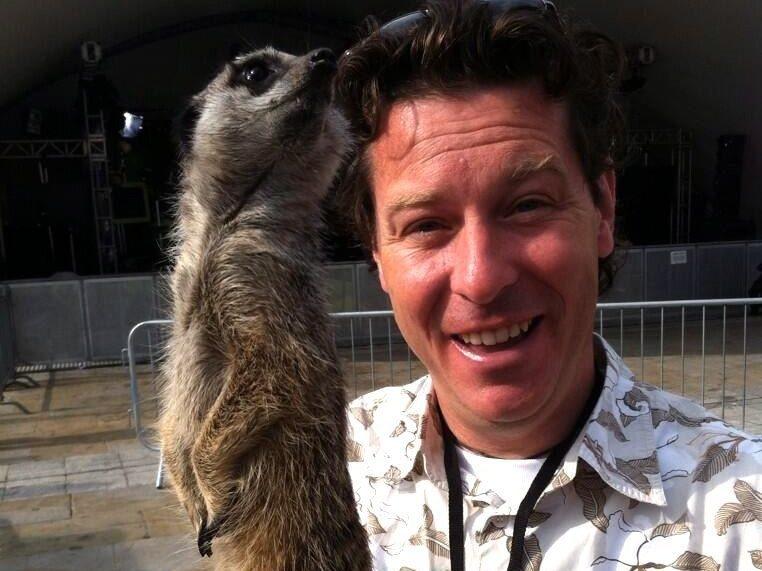 Jon holds a meerkat in his hands
