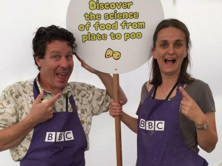 Jon and Sarah Bearchell stand together holding a lollypop sign reading 'From Plate to Poo'.