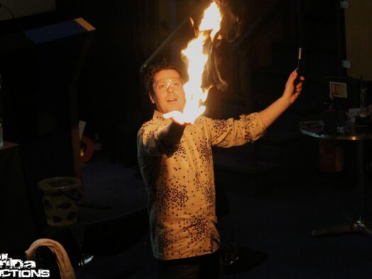 Jon stands in a dark room, holding fire aloft in his hands.