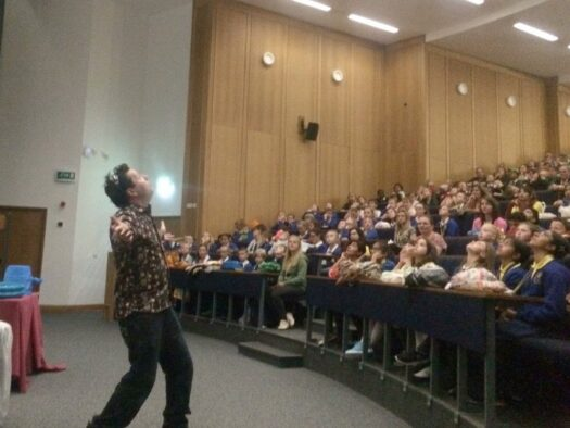 Jon stands in front of an audience and welcomes 500 school children to a show