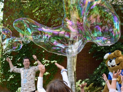 Jon creates huge bubbles for a crowd at a festival using tent poles as wands.
