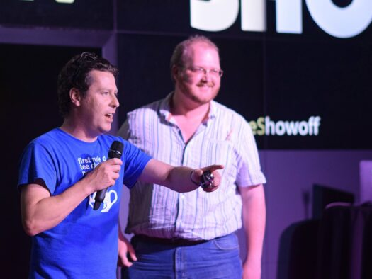 Jon interacts with the unseen audience while a participant stands on stage.