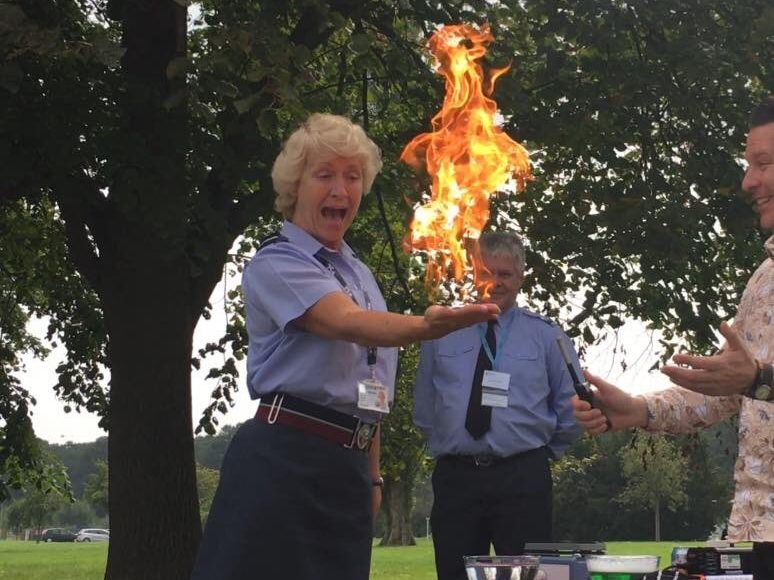 Air Commodore, Dawn McCafferty holds fire in her hand, looking surprised.