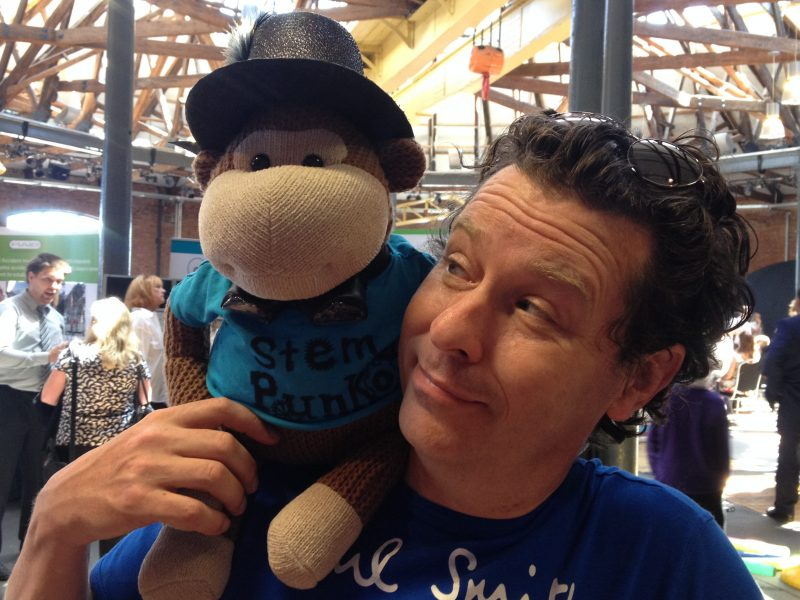 Jon looks affectionately at a toy monkey sitting on his shoulder.